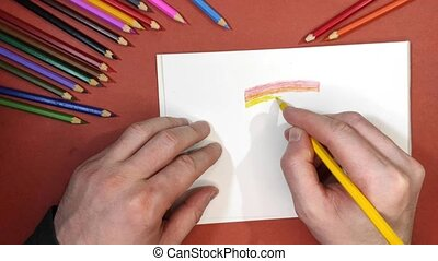 A man draws Gay Original rainbow pride flag on a piece of paper with colored pencils.High quality timelapse 4k footage