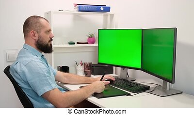 a man draws on a graphics tablet. a man working at home in front of two green monitors. remote work.