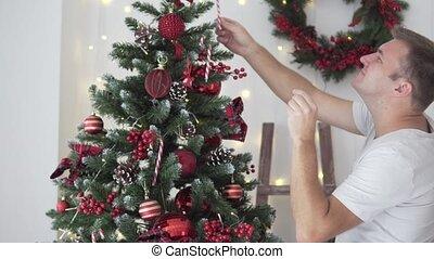 A man dresses up a Christmas tree