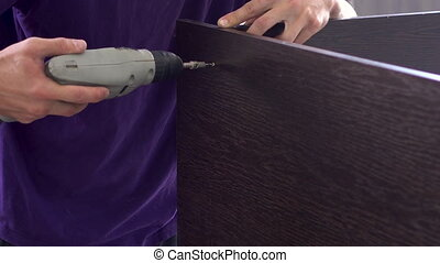 A man drills a hole in wooden planks in a furniture ...