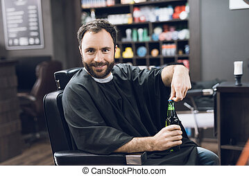 A man drinks alcohol in the hairdresser's armchair of a modern barbershop.