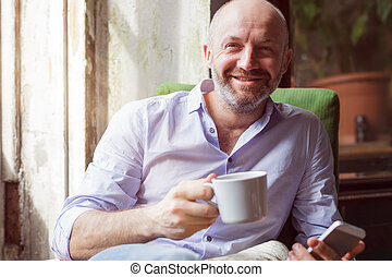 A man drinks coffee and checks the news in the phone, sitting in a chair by the window