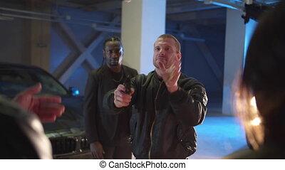 A man during a deal in a parking lot pulls a gun