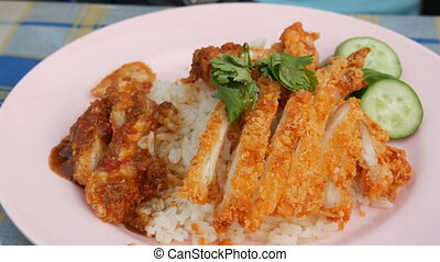 A man eats a fork with Thai food. Rice with pea pods and fried crispy chicken on breading