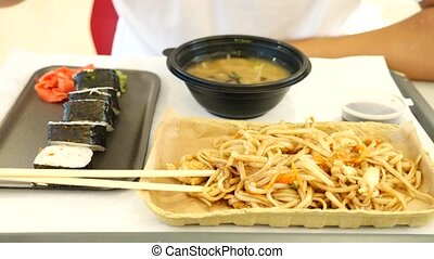 A man eats Chinese food in a fast food restaurant. 4k. Slow...