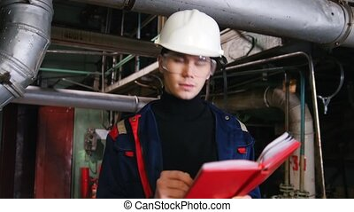 A man engineer in a helmet making notes in manufacturing...