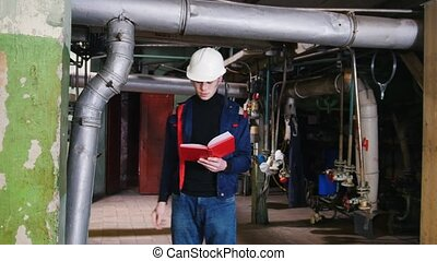 A man engineer making notes about manufacturing plant and...