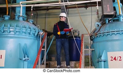 A man engineer walks to a equipment and making notes about...