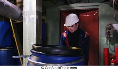 A man engineer wearing a helmet in manufacturing plant rolls a cart with an empty barrel