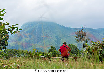 A man enjoying the mountain scenery on the edge of a cliff