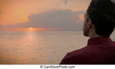 A man enjoys a cup of coffee as he watches beautiful sunrise over the ocean