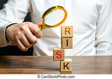 A man explores a tower of cubes with the word Risk. Search and correction of errors and failures. Risk management, cost assessment, and business and investment safety. Strengthen business resilience