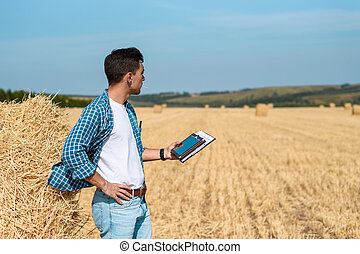A man farmer in jeans and a shirt with a tablet in his hands is in the field