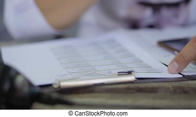 a man fills out documents or a questionnaire, a man's hands close up.