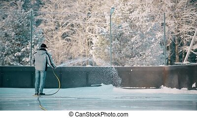 A man fills up the rink with water from a hose