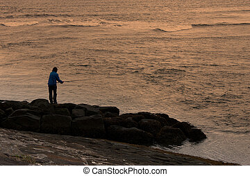 A man fishing at sunset