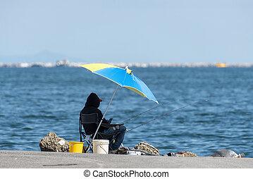 a man fishing in the gulf of la spezia under umbrella
