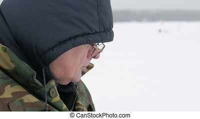 A man fishing on the lake in winter and drinking tea from a thermos. He eats biscuits with a hot drink