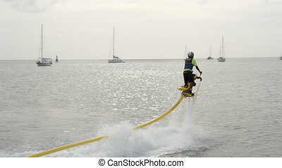 A man flying across the water with a flyboard - Wide shot of...