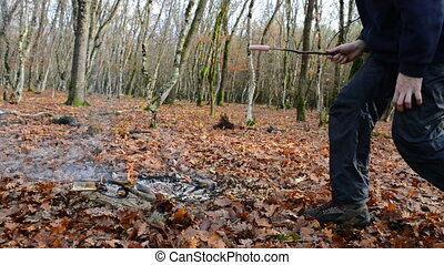 A man frying sausage on the firewood
