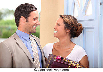 a man giving a present to his wife near house door