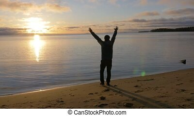 A man goes to the shore of the lake. He raises his hands up...