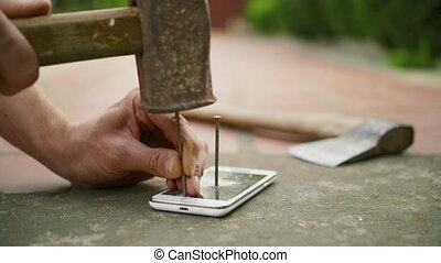 A man hammers a nail into the phone on the concrete ground in slow motion