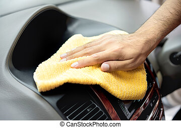 A man hand cleaning car interior with microfiber cloth - car...