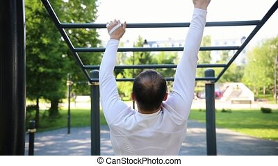 A man hanging and goes through the horizontal bars on a sports ground