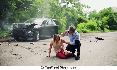 A man helping a young woman lying on the road after a car...