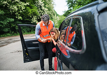 A man helping a young woman to get out of the car after a car accident.