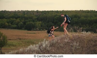 A man helps a woman to climb