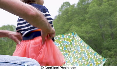 A man helps his daughter get dressed pulling up her skirt in...