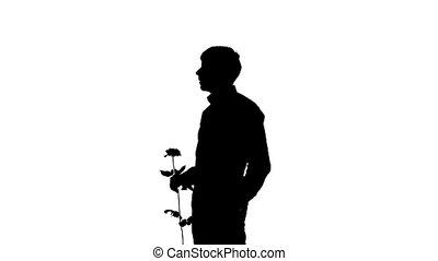 A man hiding a secret rose for his date. Silhouette. Slow motion. Close up