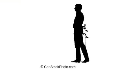 A man hiding a secret rose for his date. Silhouette - man...