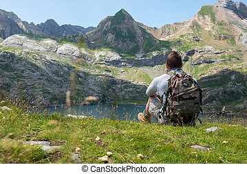 man hiker looking at Lake Estaens in the Pyrenees mountains