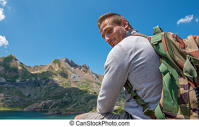 man hiker resting and looking at lake in the Pyrenees mountains
