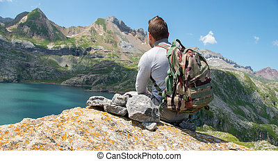 man hiker resting and looking at lake in the Pyrenees ...