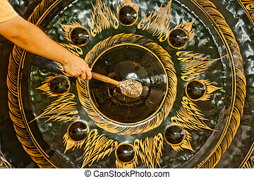 a man hit big gong in temple - Arm of a man hit big gong in...