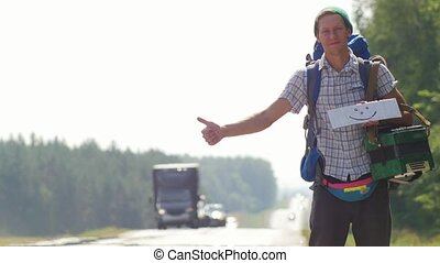 A man hitchhiker holding a white cardboard with a picture of...