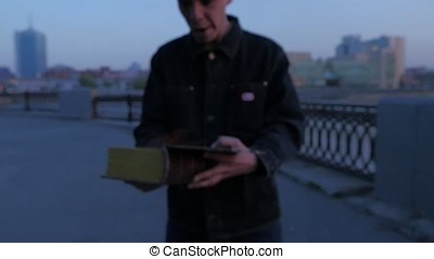 A man holding a book burning at sunset and run. Book Burning On Fire slow motion. Young Man With A Burning Book In Hand Standing On Coast Storm Clouds On. Burning Antique Book. Spiritual