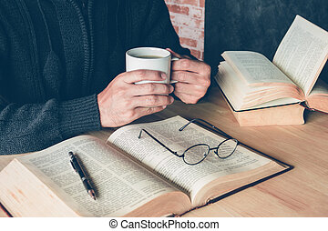 a man holding a cup of coffee with a pen and glasses on text book