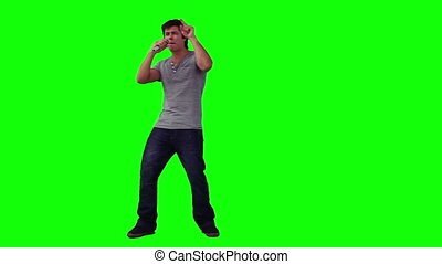 A man holding a microphone is singing in front of a green...