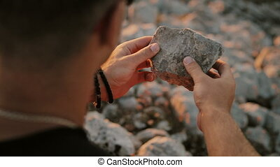 A man holding a stone in his hand closeup
