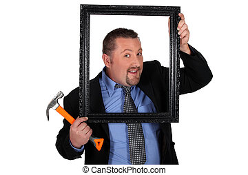 a man holding a wooden frame and a hammer