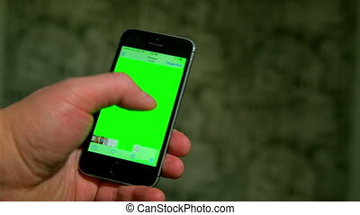a man holding smartphone with green screen in the evening.