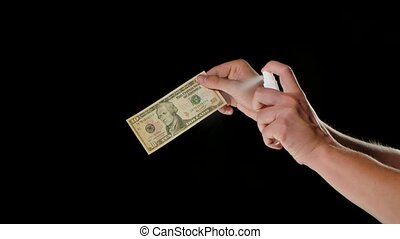 A man holds a 10 dollar bill and treats it with disinfectant antiseptic on both sides. The concept of preventing the spread of the Covid 19 coronavirus pandemic. Close up. Slow motion.