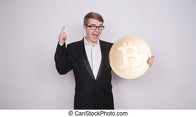 A man holds a big coin bitcoin on white background
