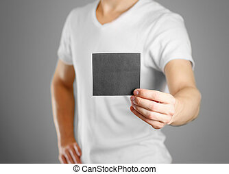 A man holds a black paper in his hand. Shows a blank flyer. Isolated