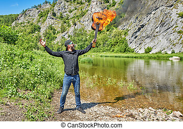 A man holds a burning guitar against the backdrop of a...
